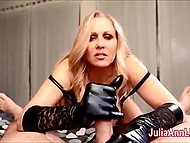 Blonde MILF Julia Ann in black gloves assiduously strokes cock with hand on camera making guy cum