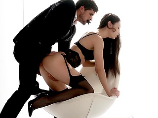 Handsome guy in costume and brunette in sexy lingerie make love in strange room
