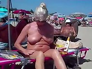 A lot of women walk on the beach being naked on a sunny day and voyeur films them