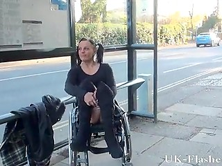 Mischievous British girl with pigtails sits in wheelchair flashing shaved pussy and tits