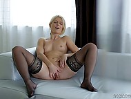 Blonde girl in black stockings needs no sex toys because her fingers help overcome excitement