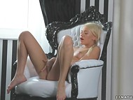 Good-looking blonde is alone at home and decides to finger bald cunny on armchair