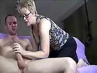 Guy jerks off sitting on the couch when experienced mature woman comes and helps him cum