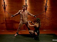 Mistress in corset and stockings orders submissive guy not to move and attaches clothespins to his body