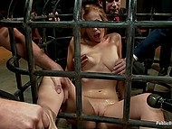 Gentleman presses Hitachi-vibrator to vagina of redhead in a cage in front of a crowd 8