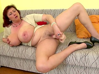 Attractive mature diva with red hair with super-big natural melons enjoys dildo in trimmed snatch