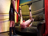 Mature mistress dominates over tied up man using different devices, chains and hot wax