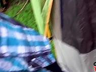 Dos jóvenes amigas acarician y se besan en la presencia de un hombre en el campamento