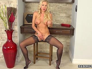 Busty blonde Katie Morgan in black stockings masturbates pussy sitting on the stool