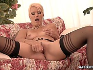 Seductive blonde in stockings uses dildo to satisfy pussy properly on the couch