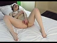 Naked chick lies alone in bed and unhurriedly buries fingers into her shaved sissy