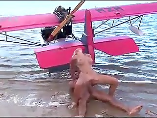 Platinum blonde beauty meets pilot of pink airplane and spreads legs on the beach for a flight