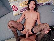 Интересная азиатская девушка в чёрных чулках массирует бо...