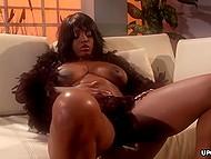 Magnifique femme noire dans boa en plumes passionnément se masturbe dans la salle de séjour