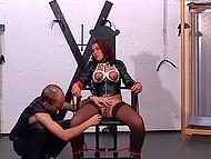 Flicka i svart läder är knuten till stolen då killen borrar hennes mun och fitta efter vax spela