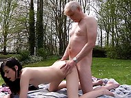 Harmaa tukka vanha mies sunbathes olla alasti, kun nuori brunette näkyy palvella hänen kukko