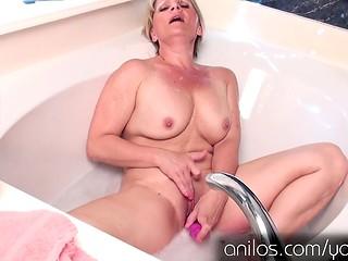 Mature Bobbie Jones fondles her pussy in bathtub