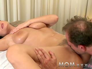 Masseur massages brunette's hairy pussy