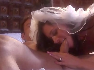 Good-looking bride in white stockings spread her legs in front of her groom