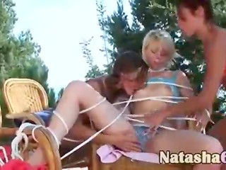 Two naughty Latina chicks stimulated their pale-skinned blonde's vagina using a dildo outdoors