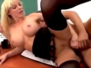 Busty blonde teacher with glasses makes love in the classroom to handsome student