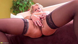 Mature blonde in stockings slowly takes clothes off and fingers her shaved peach on sofa