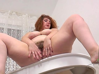 Red-haired BBW woman Katrin Porto feels sudden urge to undress and rub hairy twat in kitchen