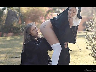 Dissolute nun with natural breasts saddles lesbian's face after licks her pussy outdoors