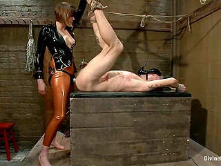 Woman dressed in latex jacket and pants uses strapon to penetrate tied up submissive's ass