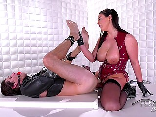 Mistress Angela White in red latex corset and stockings punishes slave drilling his ass with strapon