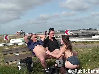 Whore in denim skirt and over-the-knee socks energetically gives handjob and blowjob to guys sitting on the bench