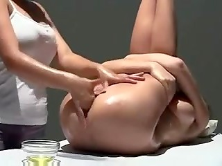 Horny masseuse touching and fingering her client's oiled pussy