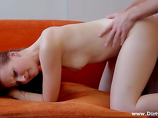 Man with a chain around neck fucks the lover on the orange couch and cums on the smooth pubis