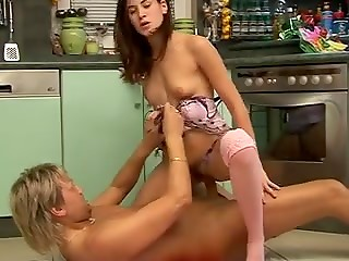 Slender babe in innocent pink stockings jerks off men's dick with her pretty legs and fucks him in the kitchen