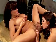 Two awesome ladies pleasing each other on the table by licking and masturbating sissies