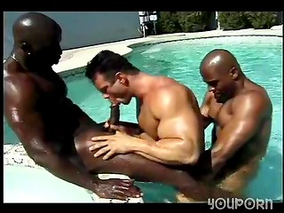 Three muscular gay guys enjoy anal sex by the poolside