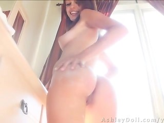 Stunning petite model Ashley Doll demonstrates her perfect natural tits and flawless ass