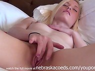 Nasty blonde playing with skillful fingers at her alluring tight vagina lying on the white bed