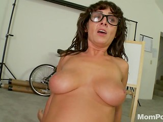Artistic girl with glasses presents pleasure on her knees before sex in cowgirl position