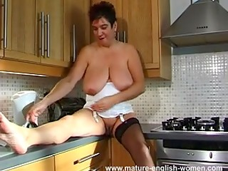 British mature woman demonstrates huge saggy boobs and touches her shaved pussy