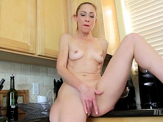 Charming lady with blond hair preparing dinner and masturbating in the kitchen