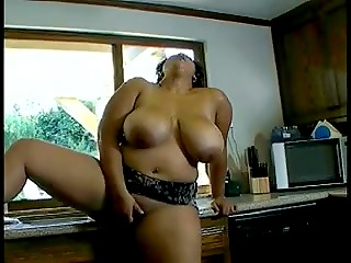 Fatty brunette bares her giant melons and starts masturbating in the kitchen