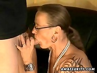 Sexy mature with glasses presents marvelous blowjob to her partner near the black sofa