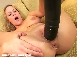 Light-haired brilliant girl tries to shove a massive black dildo into her unpierceable cunt