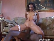 Black-skinned guy with a gigantic dick fucks his pretty girlfriend on the sofa