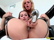 Two splendid lesbians in latex stockings are tasting their new metallic dildo on the bed