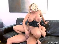 Sexy MILF with giant boobies rides pal's cock on the black sofa in the porn scene