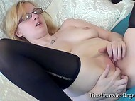 Blonde student chick with glasses rubs her shaved pussy and sensitive clit