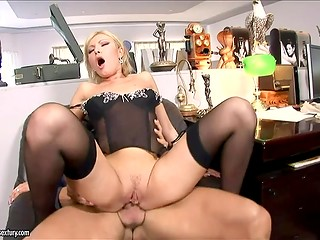 Blonde secretary with hot glasses in sexy black stockings elegantly seduces her colleague
