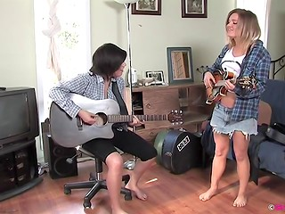 Teen blonde seduces a black-haired rocker girl during guitar lesson